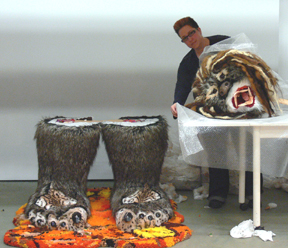 preparator beside large head and feet of a sculpture of a Sasquatch