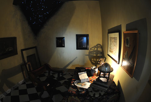 darkened room with art on walls and stars overhead