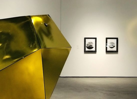 """Installation view with works by Holly Ward & Kevin Schmidt left: """"Eye of the Beholder"""" 2015. A sculpture /camera obscura: dibond, vinyl, lens, plexiglas, wood, velcro, hardware. right: """"Eye of the Beholder"""" Paper negatives"""