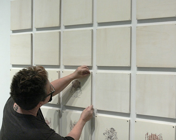 JP hanging a grid of art