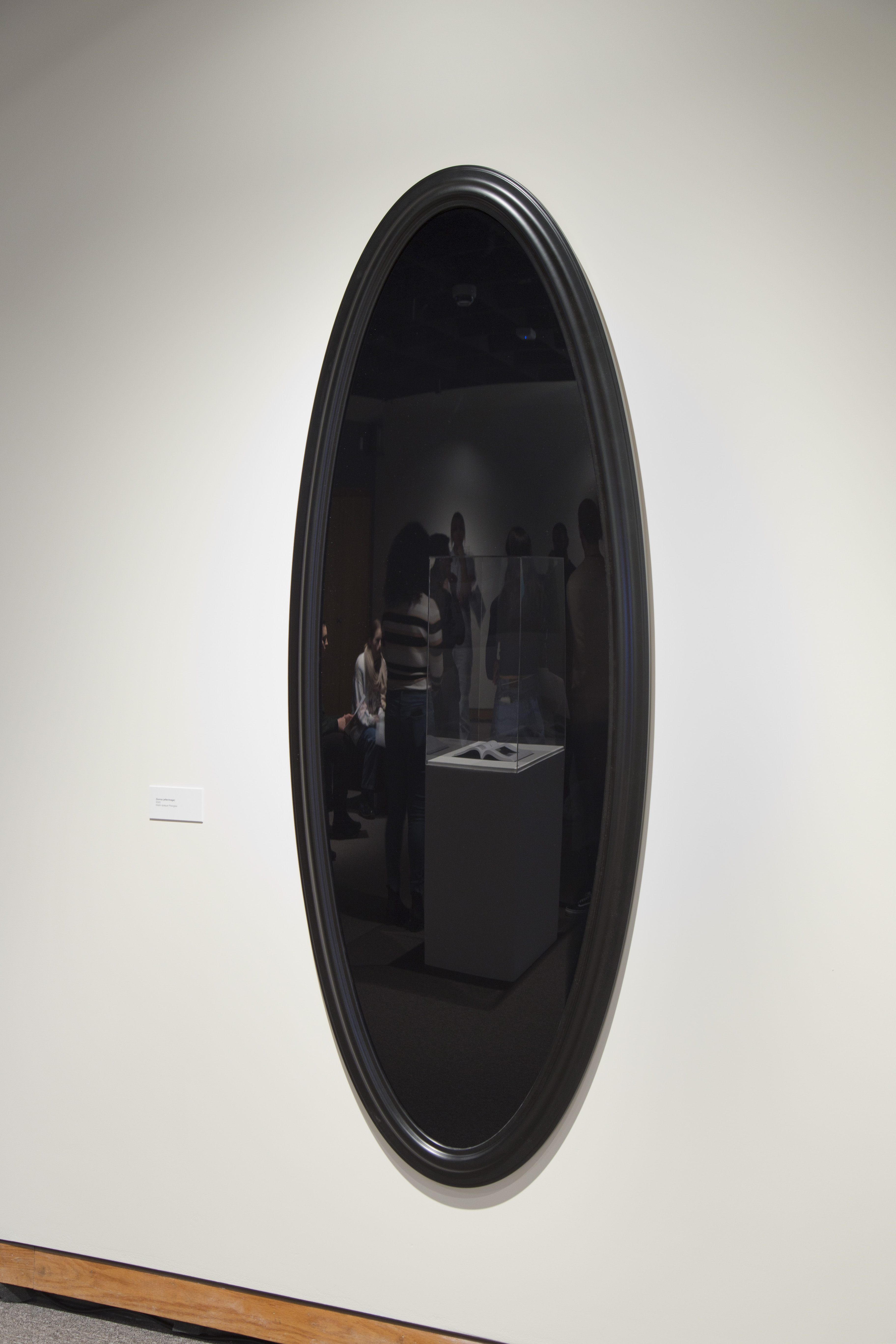 Black oval mirror by Deanna Bowen