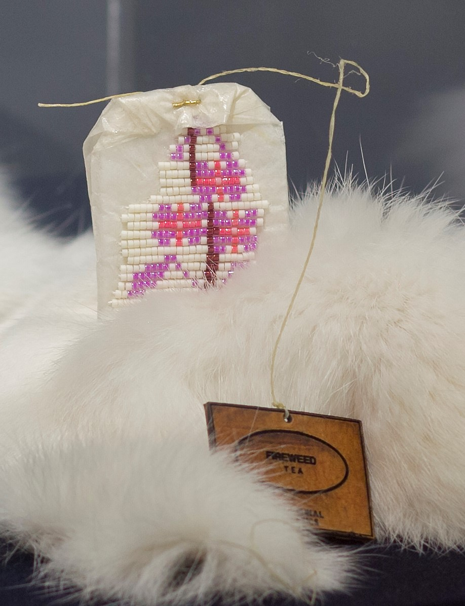 Art by Catherine Blackburn - a tea bag encrusted with white and pink beads on a fur blanket