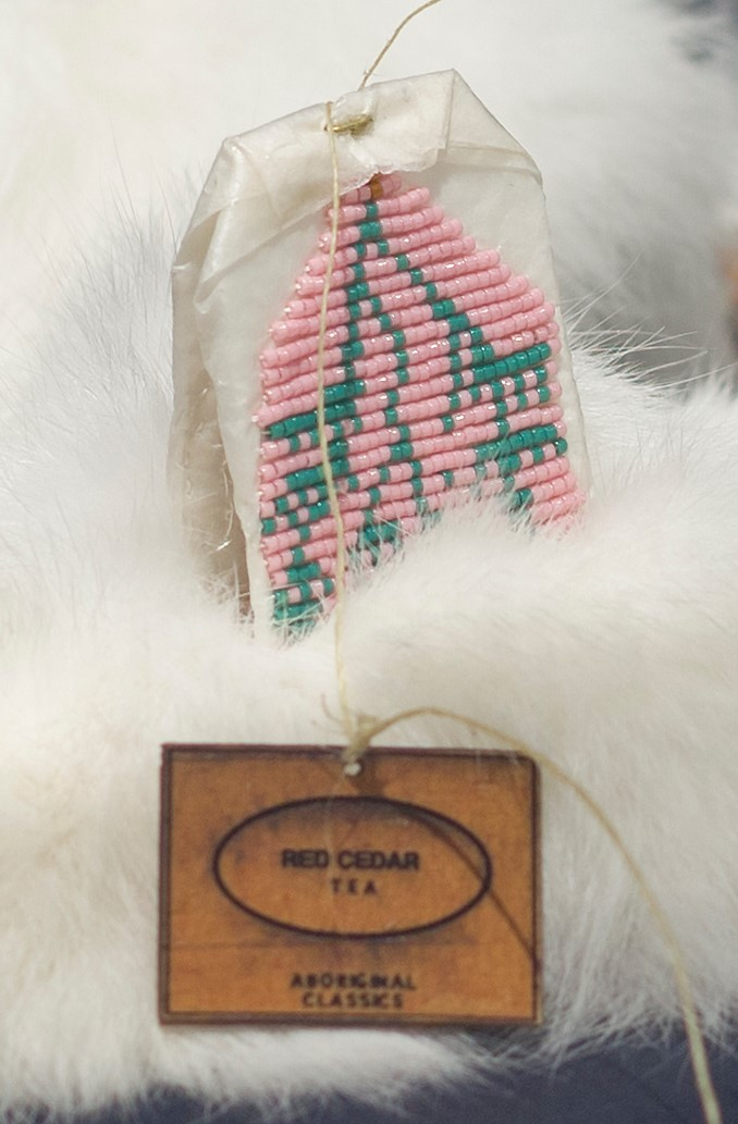 Art by Catherine Blackburn - a tea bag encrusted with pink and green beads on a fur blanket