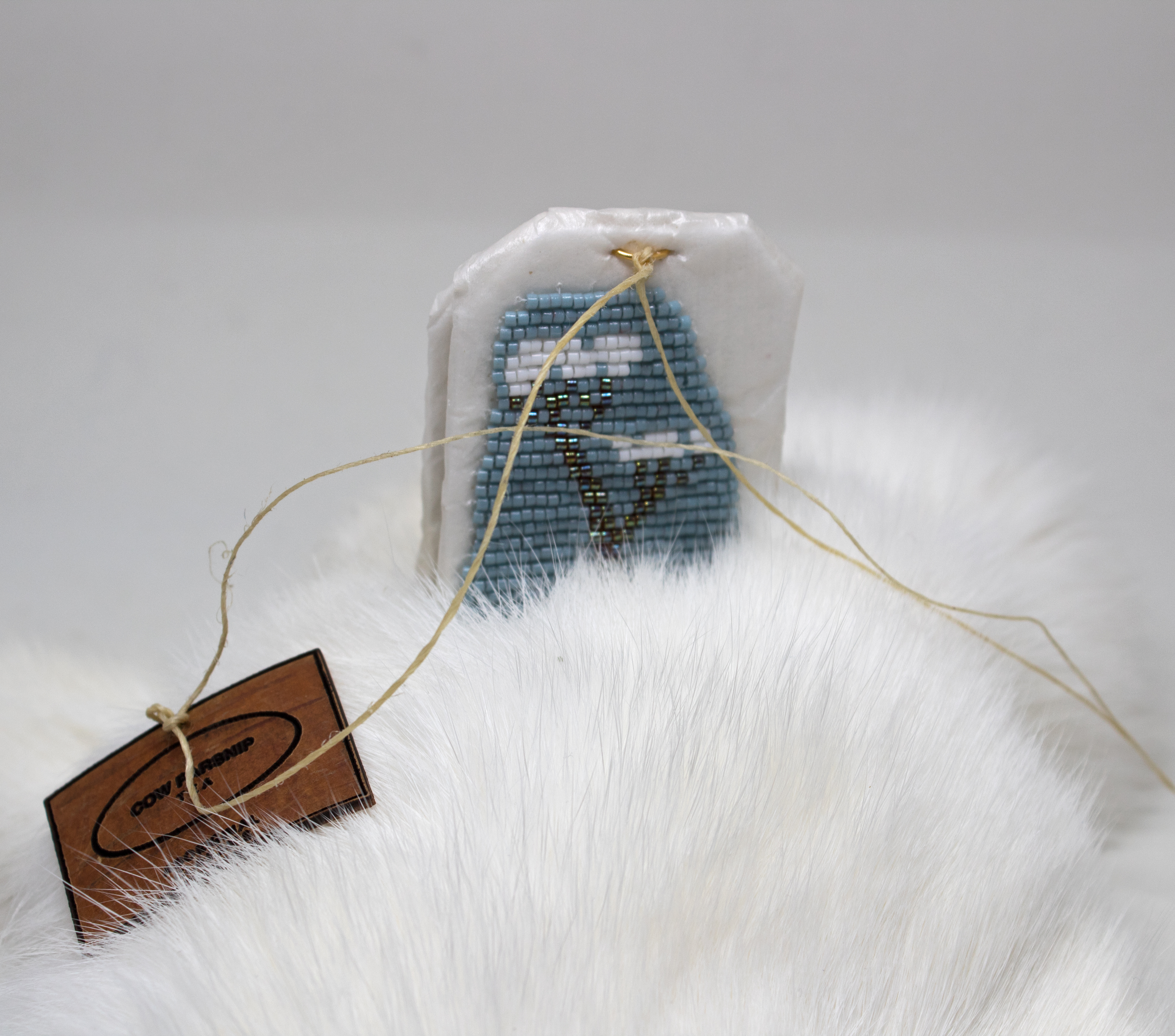 Art by Catherine Blackburn - a tea bag encrusted with blue and white beads on a fur blanket