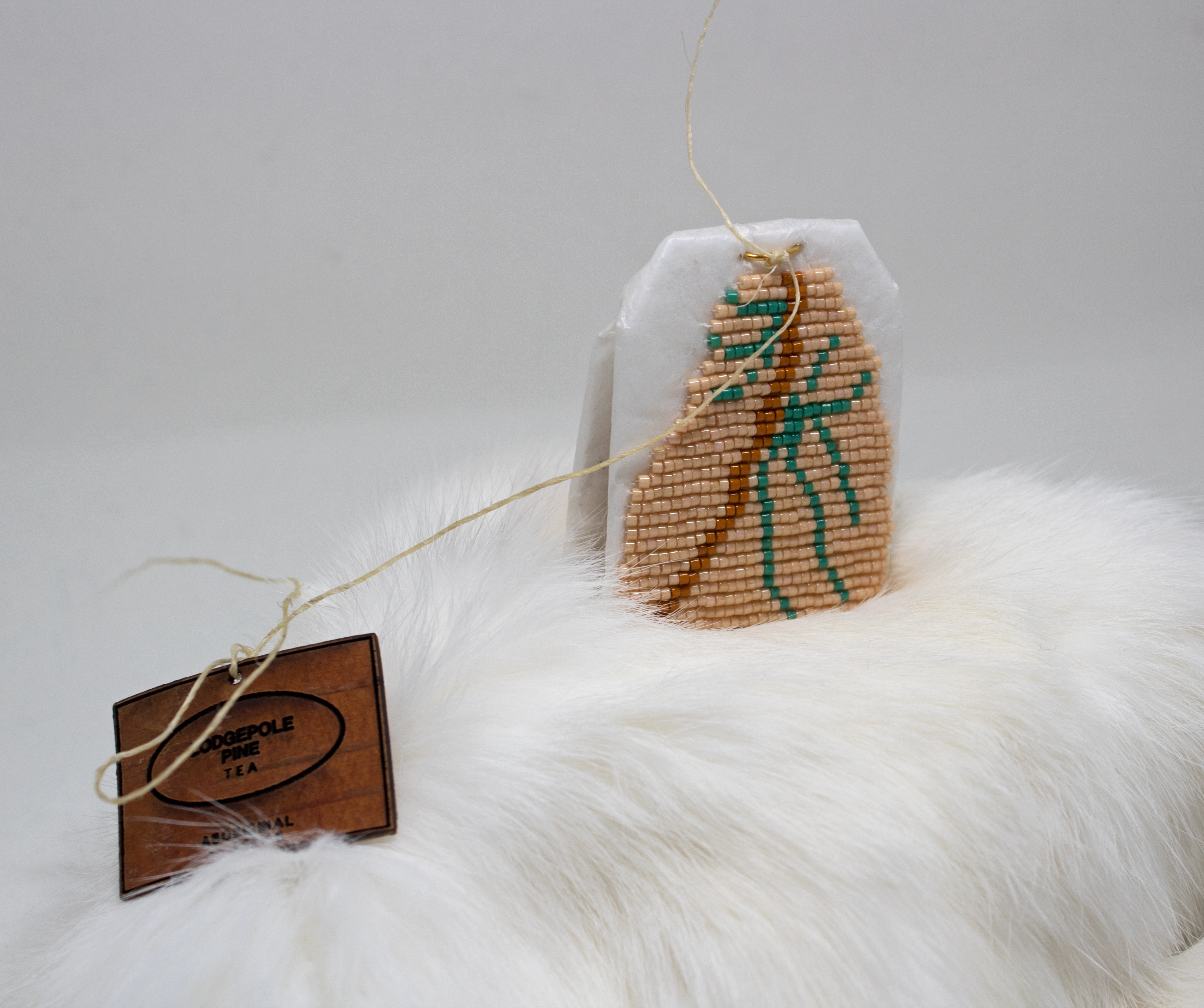 Art by Catherine Blackburn - a tea bag encrusted with beige, green and red beads on a fur blanket