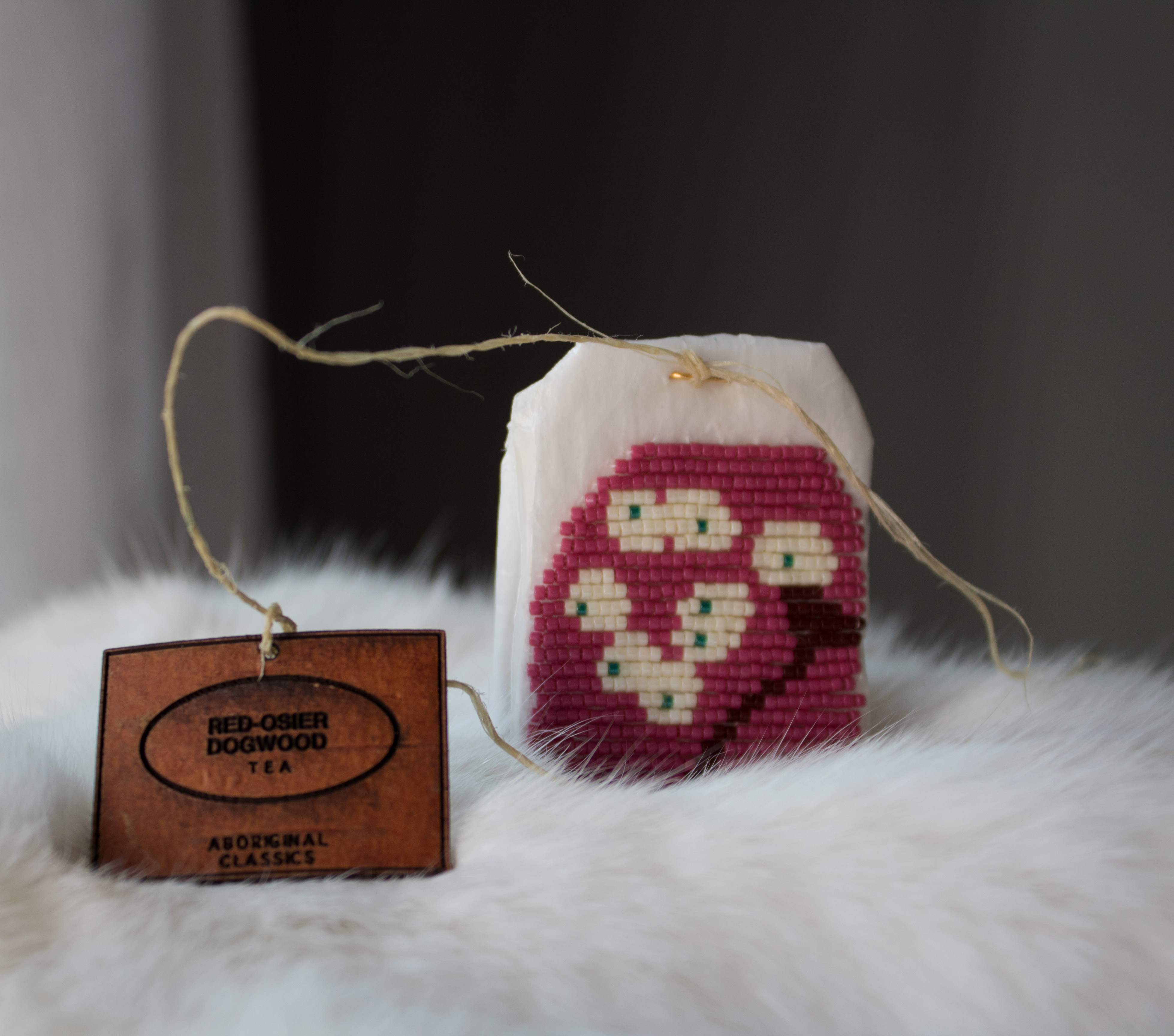 Art by Catherine Blackburn - a tea bag encrusted with red and white beads on a fur blanket