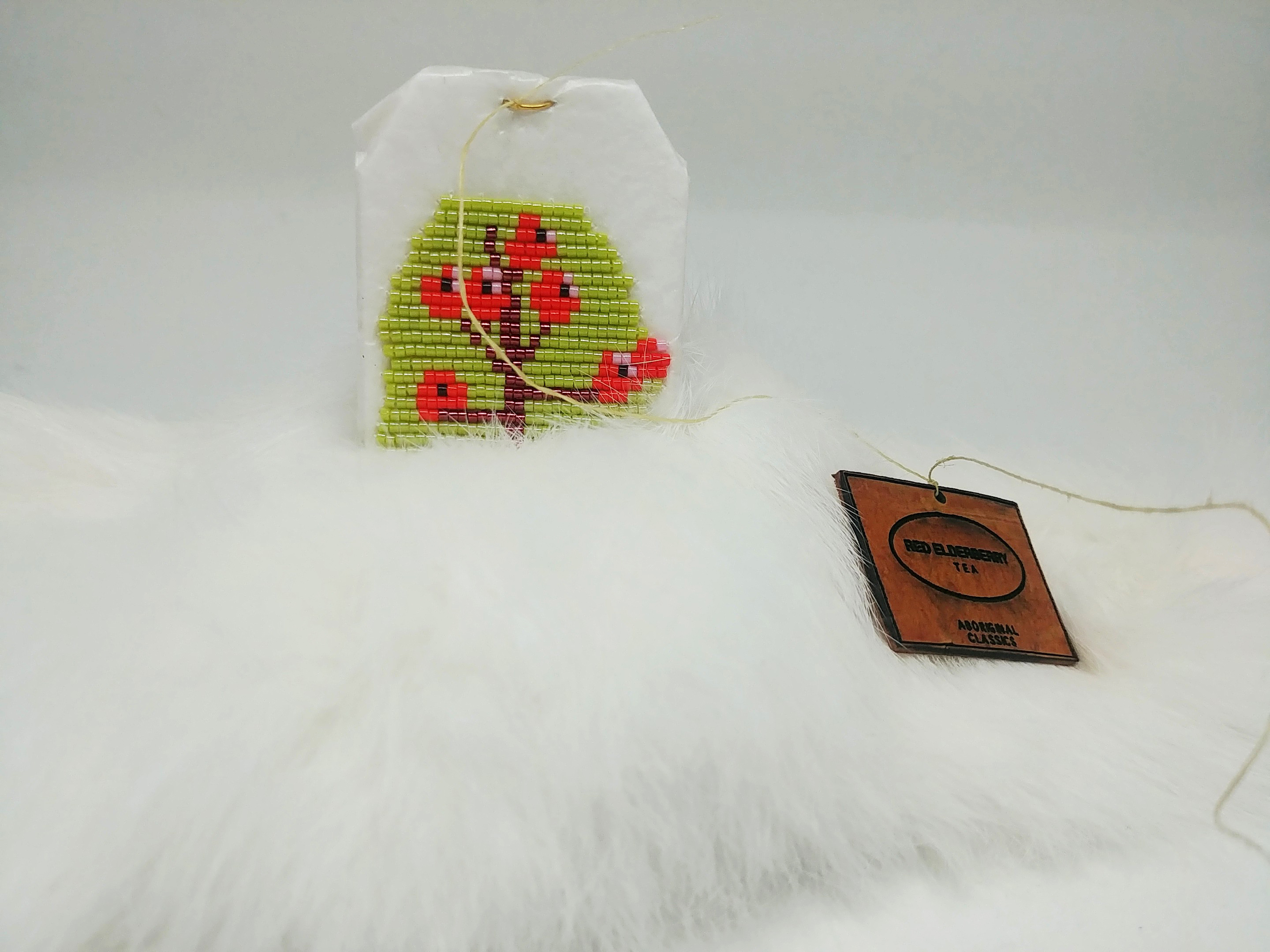 Art by Catherine Blackburn - a tea bag encrusted with red and green beads on a fur blanket