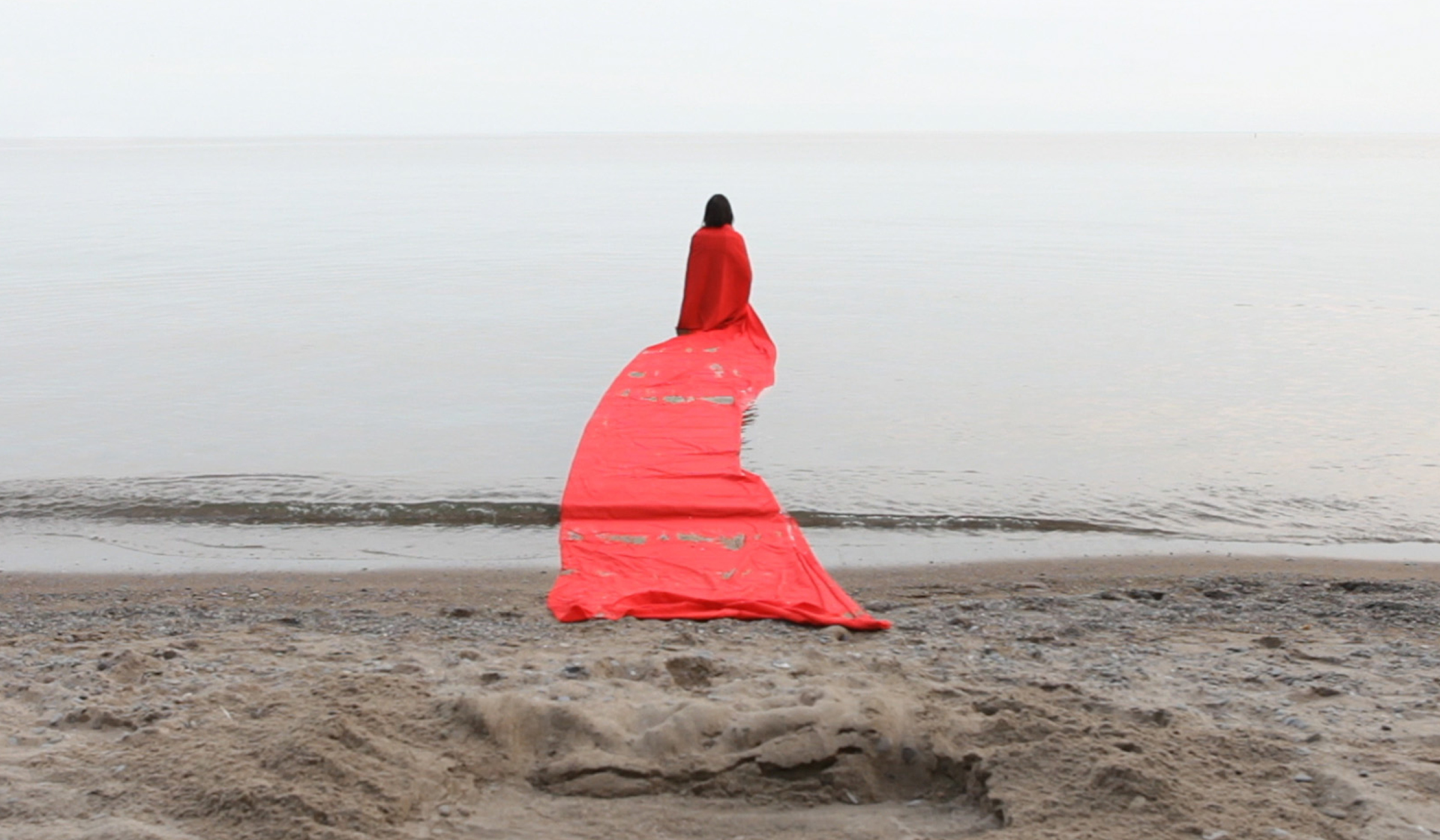 A person draped in an orangeish/reddish cloak, with a long rectangular train, walks into a body of water. The sky is grey and overcast. In the foreground is a sandy beach covered in footsteps.