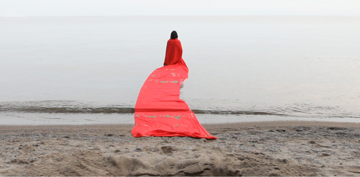 A person draped in an orangeish/reddish coat, with a long rectangular train, walks into a body of water. The sky is grey and overcast. In the foreground is a sandy beach covered in footsteps.