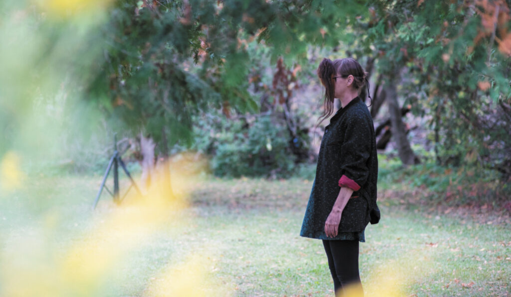 A woman in a grey coat stands in an open patch of grass surrounded by woodland and forest. She faces left, looking straight ahead but her view is obstructed by a mask she is wearingwhich appears to be made of brown hair. Blurred yellow leaves appear in the left foreground.