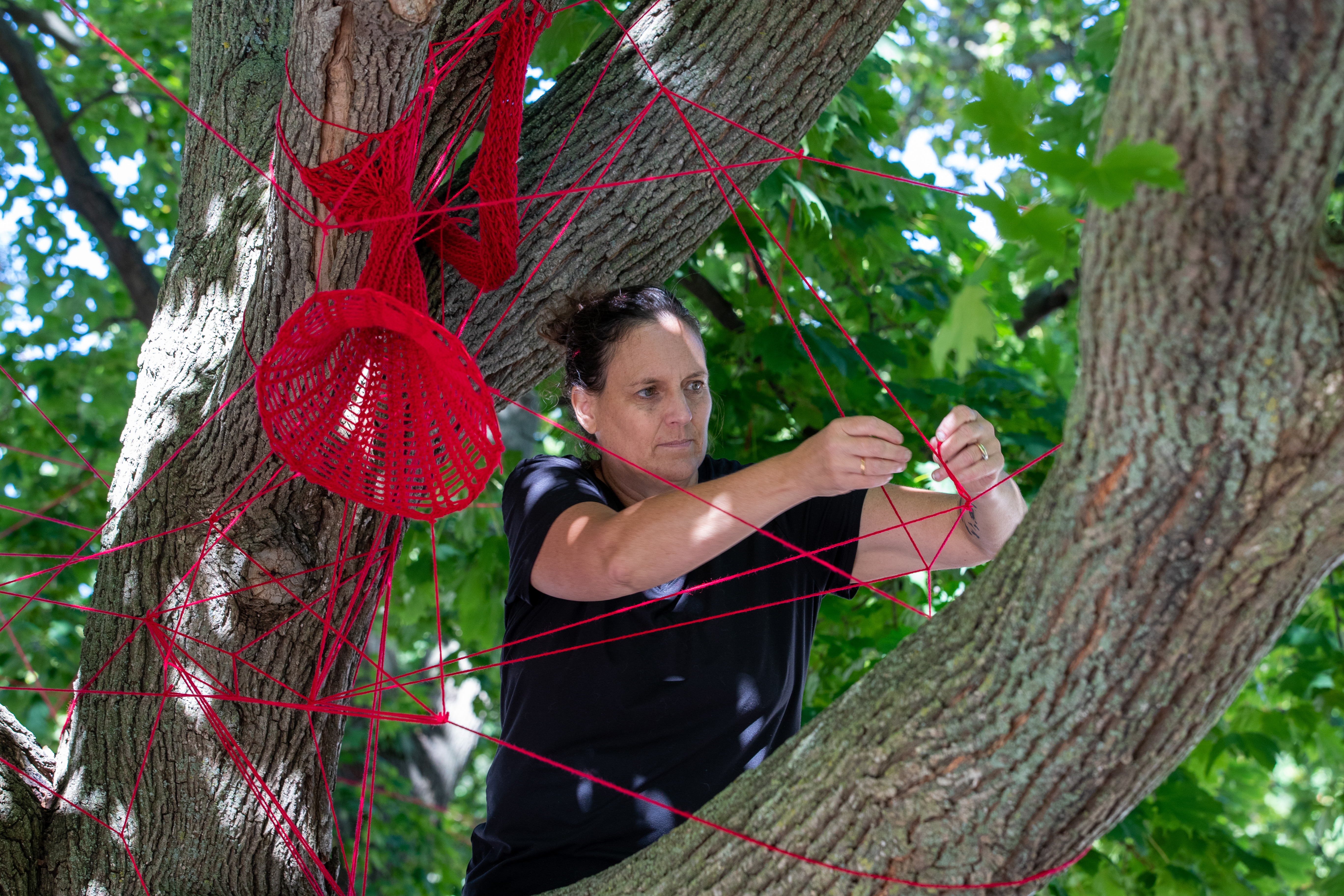 Tracey-Mae chambers installing the red string in a tree