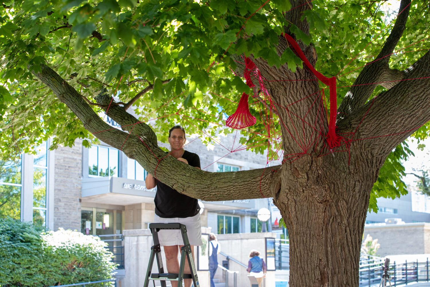 Tracey-Mae Chambers is standing on a ladder in a black t-shirt. She is shown behind a tree that is wrapped in red string part of the installation.